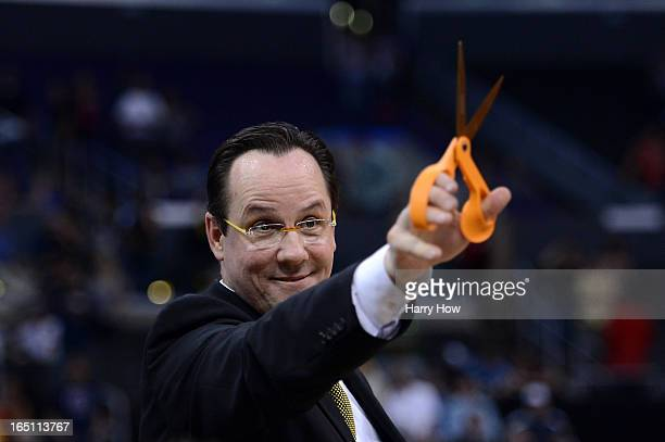 Head coach Gregg Marshall of the Wichita State Shockers holds up a pair of scissors before cutting down the net after defeating the Ohio State...