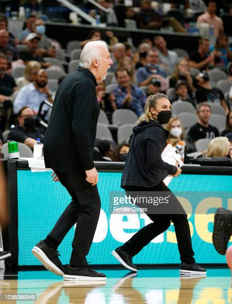 Head coach Gregg Popovich and assistant coach Becky Hammond of the San Antonio Spurs react to a non-call on a foul during the game against the...