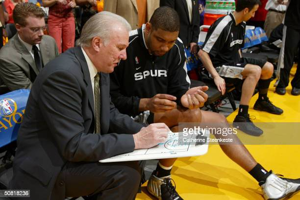 Head Coach Gregg Popovich and Tim Duncan of the San Antonio Spurs review a play on a clipboard prior the Spurs' game against the Los Angeles Lakers...