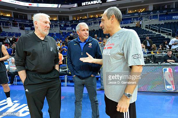 Head Coach Gregg Popovich Assistant Coach Ettore Messina of the San Antonio Spurs and Zeljko Obradovic Fenerbahce of Ulker talk prior to a game as...