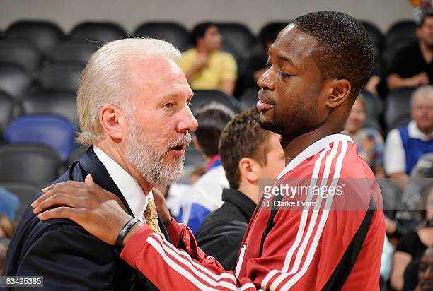 Head coach Gregg Popovich of the San Antonio Spurs talks with Dwyane Wade of the Miami Heat before a game against Miami Heat October 24 2008 at the...