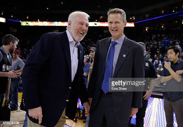 Head coach Gregg Popovich of the San Antonio Spurs talks with head coach Steve Kerr of the Golden State Warriors before their game at ORACLE Arena on...