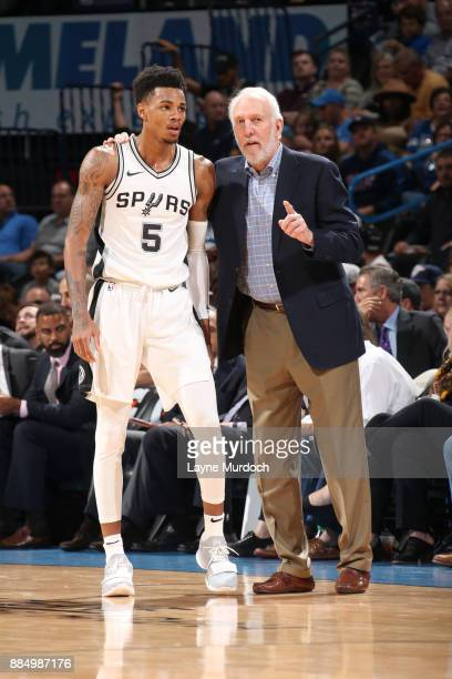 Head Coach Gregg Popovich of the San Antonio Spurs talks with Dejounte Murray of the San Antonio Spurs during the game against the Oklahoma City...
