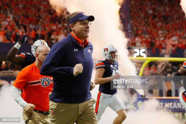 Head coach Gus Malzahn of the Auburn Tigers runs out of the tunnel with his team prior to the game against the Auburn Tigers in the SEC Championship...