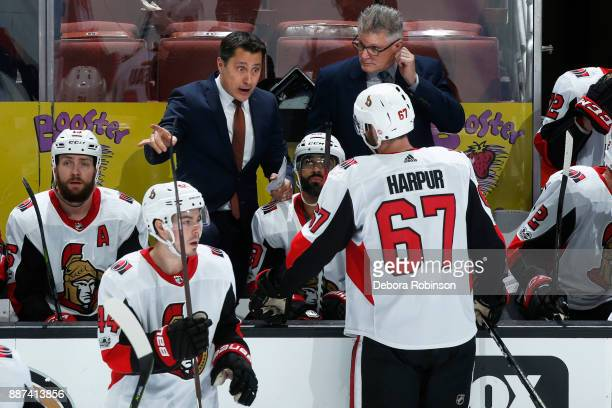 Head coach Guy Boucher of the Ottawa Senators chats with Ben Harpur prior to a faceoff during the game against the Anaheim Ducks on December 6 2017...