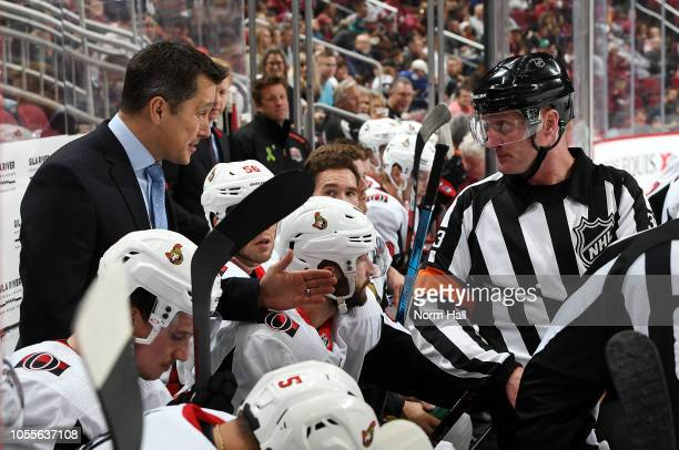 Head coach Guy Boucher of the Ottawa Senators talks with referee Kevin Pollock during second period action against the Arizona Coyotes at Gila River...