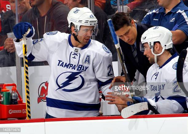 Head coach Guy Boucher of the Tampa Bay Lightning talks to Martin St Louis and Trevor Smith of the Lightning on the bench at an NHL hockey game...