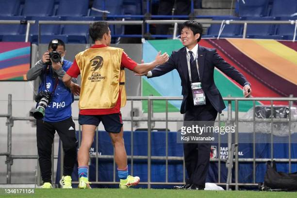 Head coach Hajime Moriyasu of Japan celebrates his side's 2-1 victory with Yuto Nagatomo during the FIFA World Cup Asian qualifier final round Group...