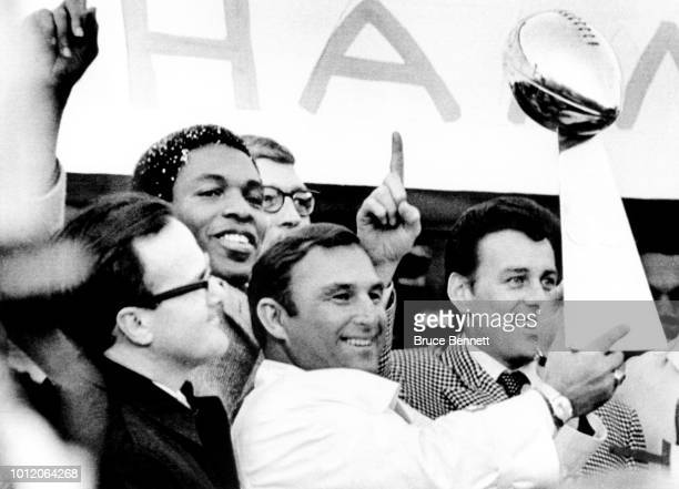 Head coach Hank Stram of the Kansas City Chiefs holds the Super Bowl Trophy as owner Lamar Hunt Otis Taylor and Len Dawson look on during the Chiefs...