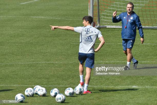 Head coach HansDieter Flick of Bayern Muenchen and Robert Lewandowski of Bayern Muenchen gesture during a training session at Saebener Strasse...