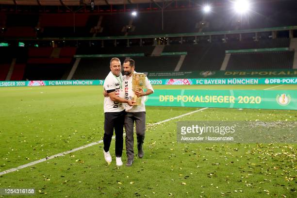 Head coach Hans-Dieter Flick of FC Bayern Muenchen and Hasan Salihamidzic, Sporting Director of FC Bayern Muenchen pose with the trophy in...