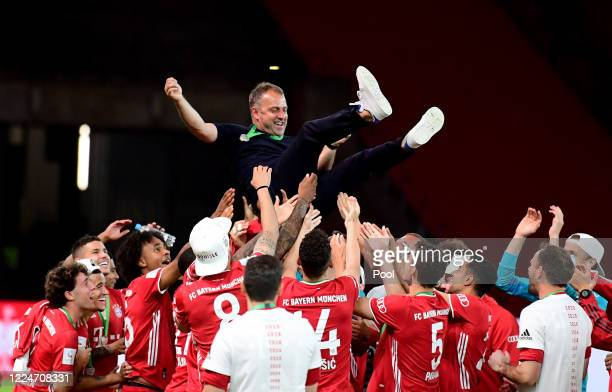Head Coach Hans-Dieter Flick of FC Bayern Muenchen is thrown in the air by the players after winning the DFB Cup final match between Bayer 04...