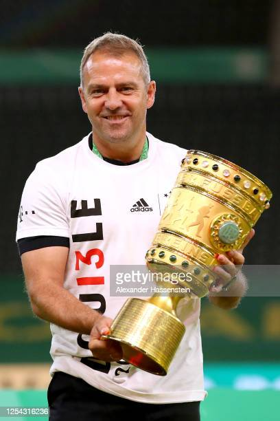 Head coach Hans-Dieter Flick of FC Bayern Muenchen poses with the trophy in celebration after the DFB Cup final match between Bayer 04 Leverkusen and...