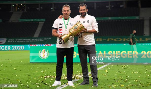 Head coach Hansi Flick of Bayern Muenchen and Sports director Hasan Salihamidzic are seen with the trophy during the DFB Cup final match between...