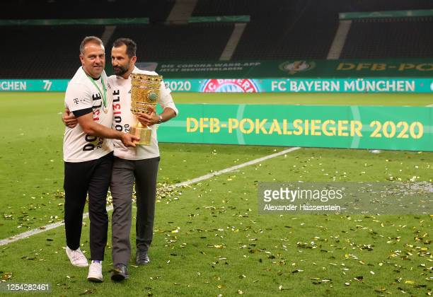 Head coach Hansi Flick of FC Bayern Muenchen and Hasan Salihamidzic, Sporting Director of FC Bayern Muenchen pose with the trophy in celebration...