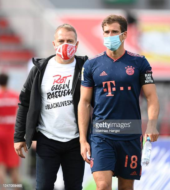 Head coach Hansi Flick of Muenchen wears a shirt with a message reading 'Red against racism #blacklivesmatter' as he walks next to Leon Goretzka...