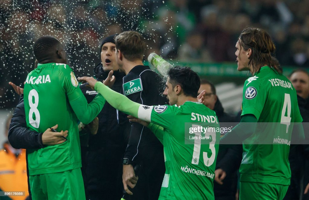 Head coach Heiko Herrlich of Leverkusen argues with Denis Zakaria of Moenchegladbach and gets hit by a glass of beer during the DFB Cup match between Borussia Moenchengladbach and Bayer Leverkusen at Borussia-Park on December 20, 2017 in Moenchengladbach, Germany.