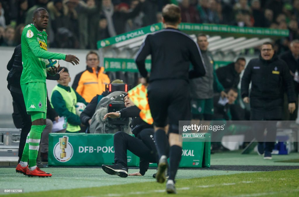 Head coach Heiko Herrlich of Leverkusen falls down next to Denis Zakaria of Moenchegladbach during the DFB Cup match between Borussia Moenchengladbach and Bayer Leverkusen at Borussia-Park on December 20, 2017 in Moenchengladbach, Germany.