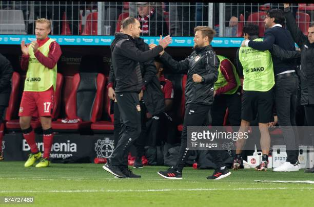 Head coach Heiko Herrlich of Leverkusen gives cocoach Nico Schneck his hand during the Bundesliga match between Bayer 04 Leverkusen and 1 FC Koeln at...