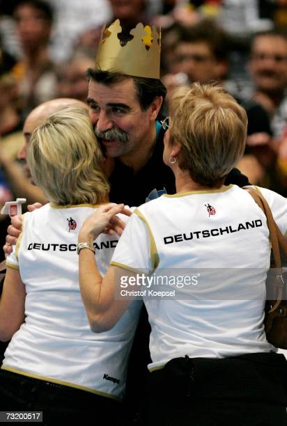Head coach Heiner Brand is kissed by his wife Christel and a friend after winning the IHF World Championship final between Germany and Poland at the...