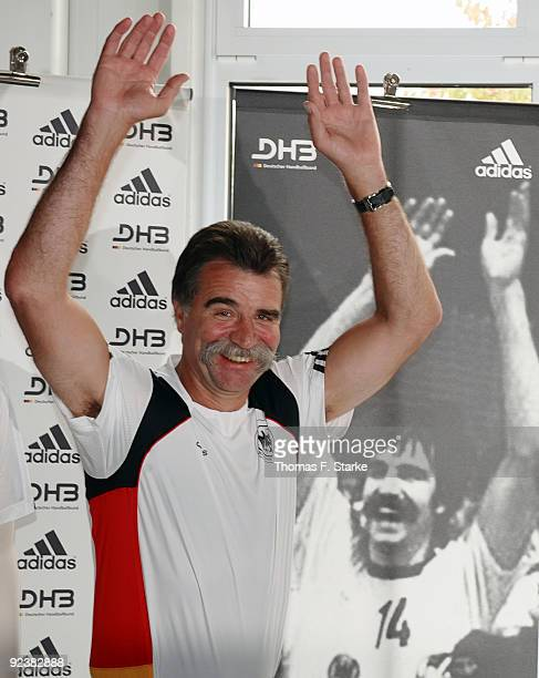 Head coach Heiner Brand presents the new national shirt infront of an old photo of himself during the Team presentation of the German Handball...
