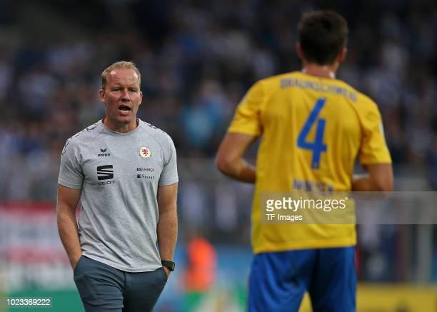 Head coach Henrik Pedersen of Eintracht Braunschweig speaks with Malte Amundsen of Eintracht Braunschweig during the DFB Cup first round match...