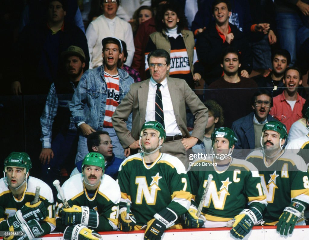 Head coach Herb Brooks (1937-2003) of the Minnesota North Stars watches the action along with his players Basil McRae #17, Dirk Graham #21, Neal Broten #7, captain Craig Hartsburg #4 and Terry Ruskowski #8 during an NHL game against the Philadelphia Flyers on December 23, 1987 at the Spectrum in Philadelphia, Pennsylvania.