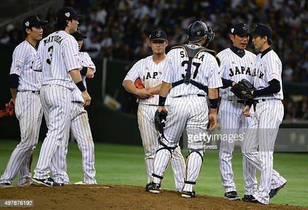 Head coach Hiroki Kokubo of Japan passes the ball to pitcher Hirotoshi Masui in the top of ninth inning during the WBSC Premier 12 semi final match...
