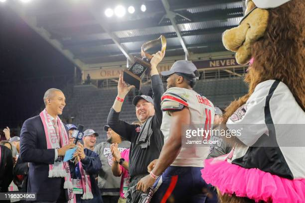 Head coach Hugh Freeze of the Liberty Flames lifts the trophy after defeating the Georgia Southern Eagles in the 2019 Cure Bowl at Exploria Stadium...
