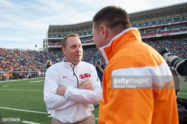 Head coach Hugh Freeze of the Mississippi Rebels talks with head coach Butch Jones of the Tennessee Volunteers prior to their game on October 18 2014...