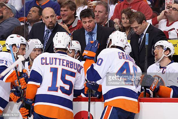Head coach Jack Capuano of the New York Islanders talks with Cal Clutterbuck and Michael Grabner during a time out from the NHL game against the...