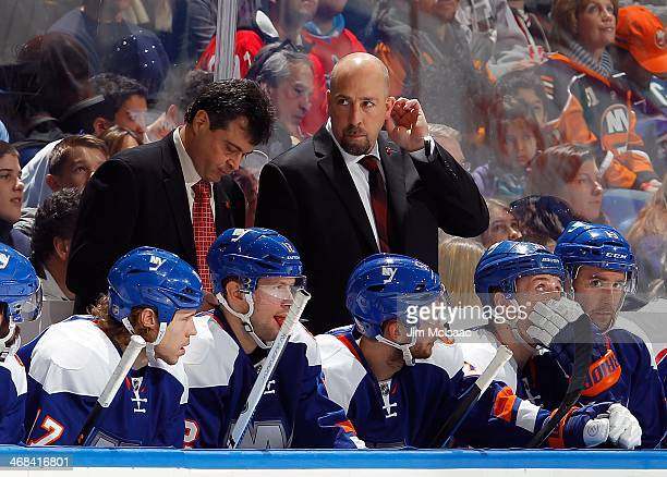 Head coach Jack Capuano talks to Assistant Coach Brent Thompson on the bench during the game against the Colorado Avalanche on February 8 2014 at...
