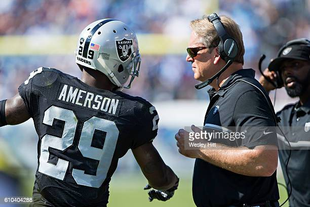 Head Coach Jack Del Rio talks with David Amerson of the Oakland Raiders during a timeout during a game against the Tennessee Titans at Nissan Stadium...