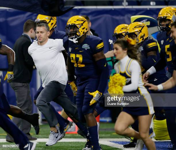 Head coach Jason Candle of the Toledo Rockets leads his players including defensive end Daniel Davis of the Toledo Rockets onto the field during the...