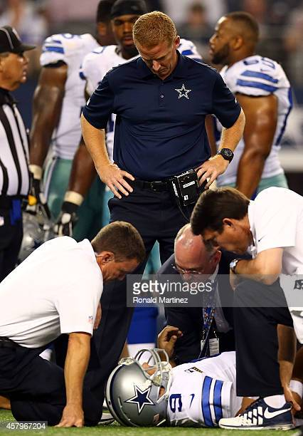 Head coach Jason Garrett of the Dallas Cowboys and team personnel attend to Tony Romo of the Dallas Cowboys after he was sacked by Keenan Robinson of...