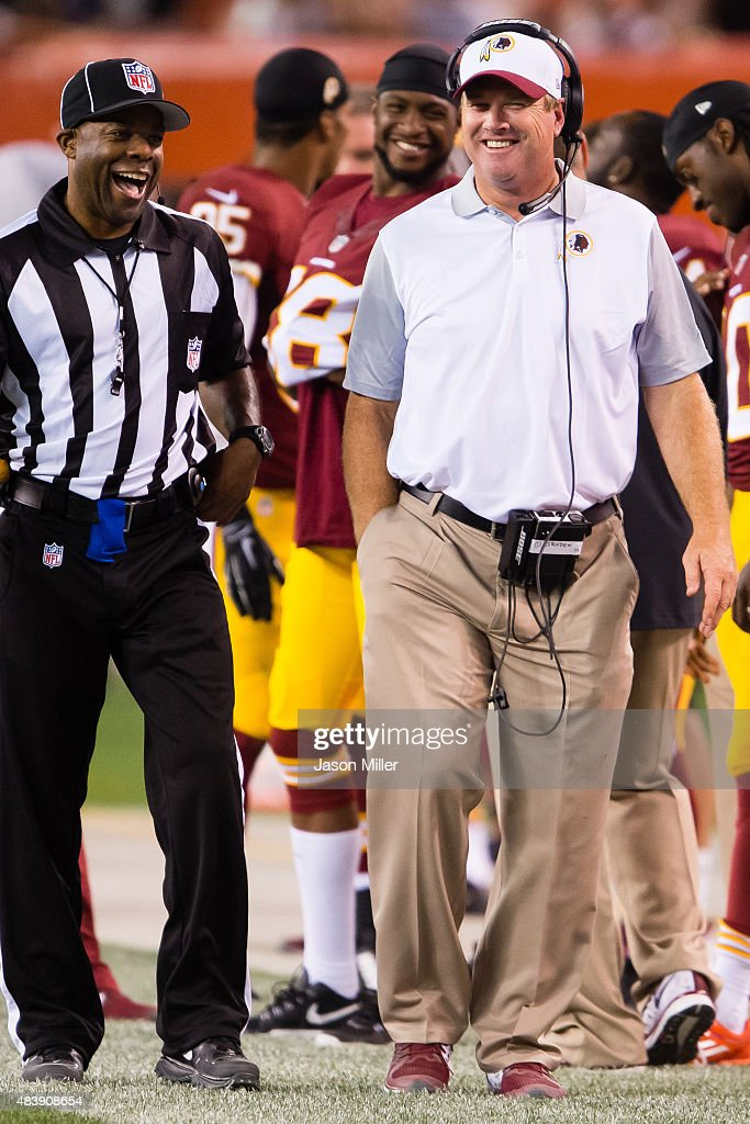 Head coach Jay Gruden of the Washington Redskins jokes with an official on the sidelines during the second half against the Cleveland Browns at FirstEnergy Stadium on August 13, 2015 in Cleveland, Ohio. The Redskins defeated the Browns 20-17.