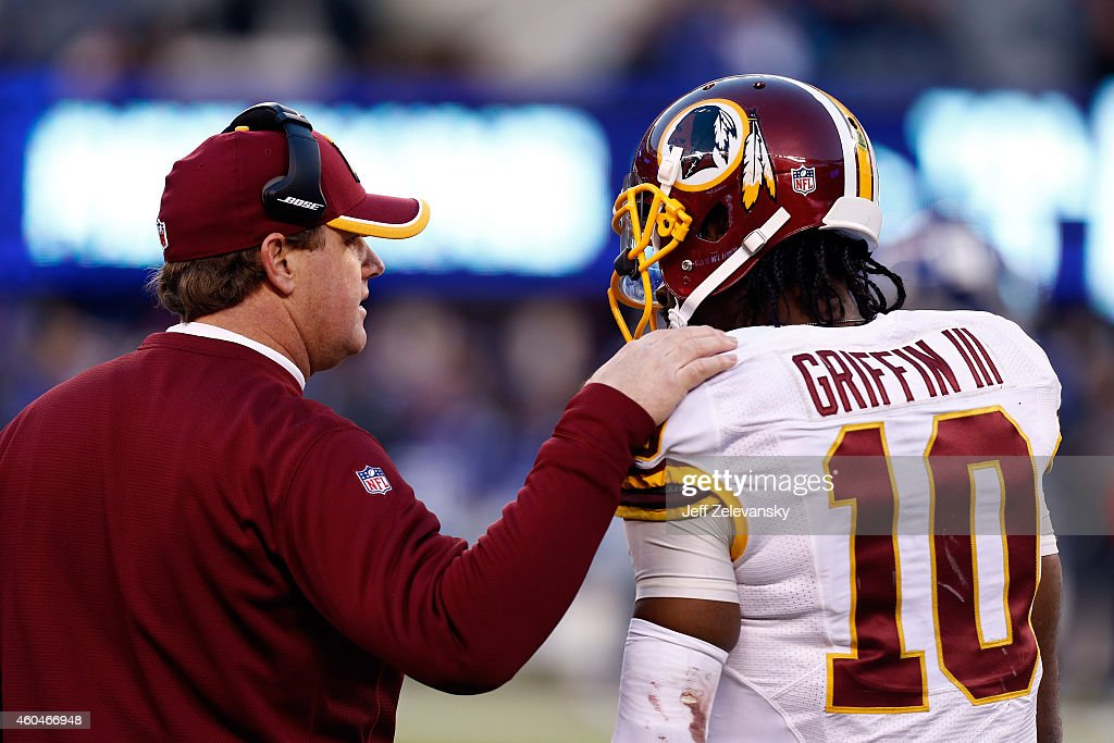 Head coach Jay Gruden talks with Robert Griffin III #10 of the Washington Redskins on the sidelines against the New York Giants during their game at MetLife Stadium on December 14, 2014 in East Rutherford, New Jersey.