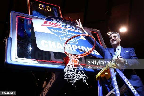 Head coach Jay Wright of the Villanova Wildcats cuts a piece of the net after defeating the Creighton Bluejays to win the Big East Basketball...