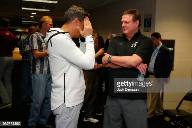 Head coach Jay Wright of the Villanova Wildcats talks with head coach Bill Self of the Kansas Jayhawks during Media Day for the NCAA Men's Final Four...