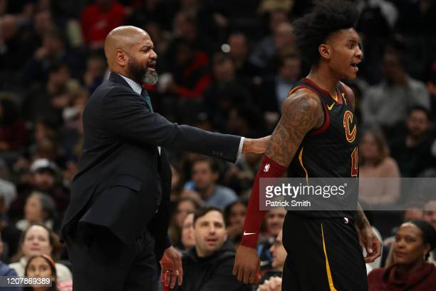 Head coach J.B. Bickerstaff of the Cleveland Cavaliers walks Kevin Porter Jr. #4 of the Cleveland Cavaliers off of the court after Porter Jr. Was...