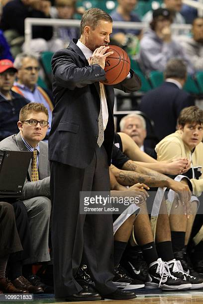 Head coach Jeff Bzdelik of the Wake Forest Demon Deacons squeezes a basketball while playing against the Boston College Eagles during the first round...