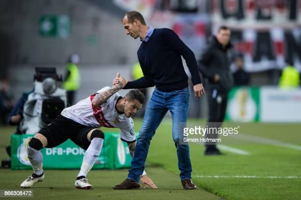 Head coach Jeff Strasser of Kaiserslautern helps Daniel Ginczek of Stuttgart during the DFB Cup match between 1 FC Kaiserslautern and VfB Stuttgart...