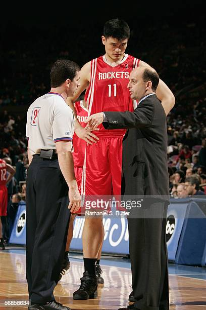 Head coach Jeff Van Gundy of the Houston Rockets talks with NBA official Tim Donaghyas as Yao Ming listens on to the conversations during a game...