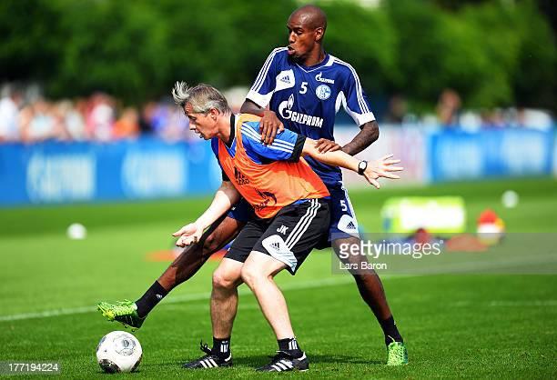 Head coach Jens Keller is challenged by Felipe Santana during a FC Schalke 04 training session on August 22 2013 in Gelsenkirchen Germany