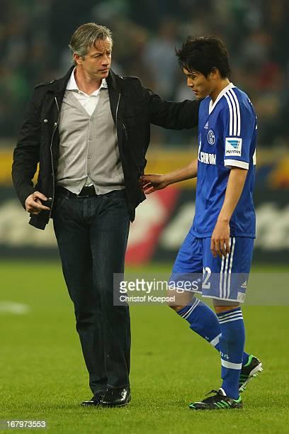 Head coach Jens Keller of Schalke cares of Atsuto Uchida of Schalke after his injury during the Bundesliga match between Borussia Moenchengladbach...