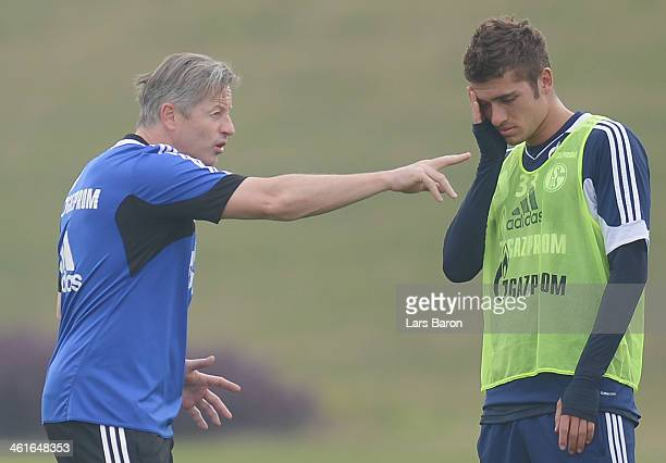 Head coach Jens Keller speaks to Roman Neustaedter during a FC Schalke 04 training session at ASPIRE Academy for Sports Excellence on January 10 2014...