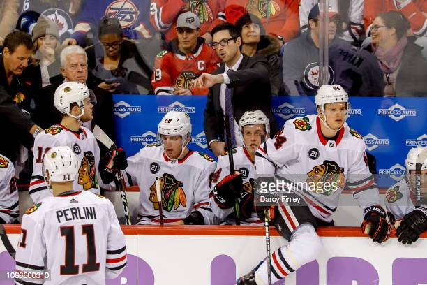 Head Coach Jeremy Colliton of the Chicago Blackhawks gives directions to Alex DeBrincat at the bench during a second period stoppage in play against...