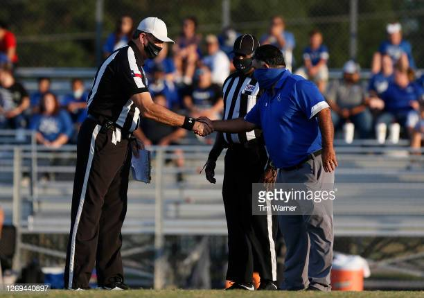 Head coach Jerry Long of Edna Cowboys talks with referees while wearing masks before the game against the East Bernard Brahmas on August 28, 2020 in...