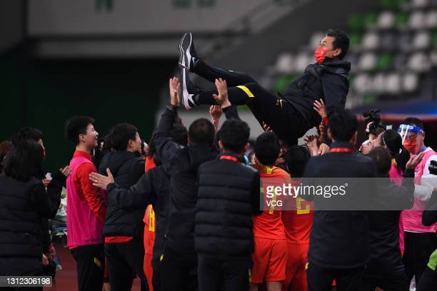 Head coach Jia Xiuquan of China is thrown into the air by his players after the Tokyo Olympics Women's Football Asian Final Qualifier 2nd leg match...