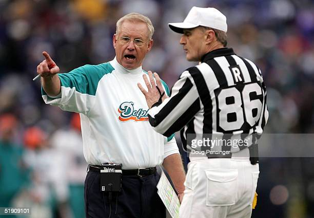 Head coach Jim Bates of the Miami Dolphins protests a call with referee Bernie Kukar as the Baltimore Ravens defeated the Dolphins 3023 during NFL...